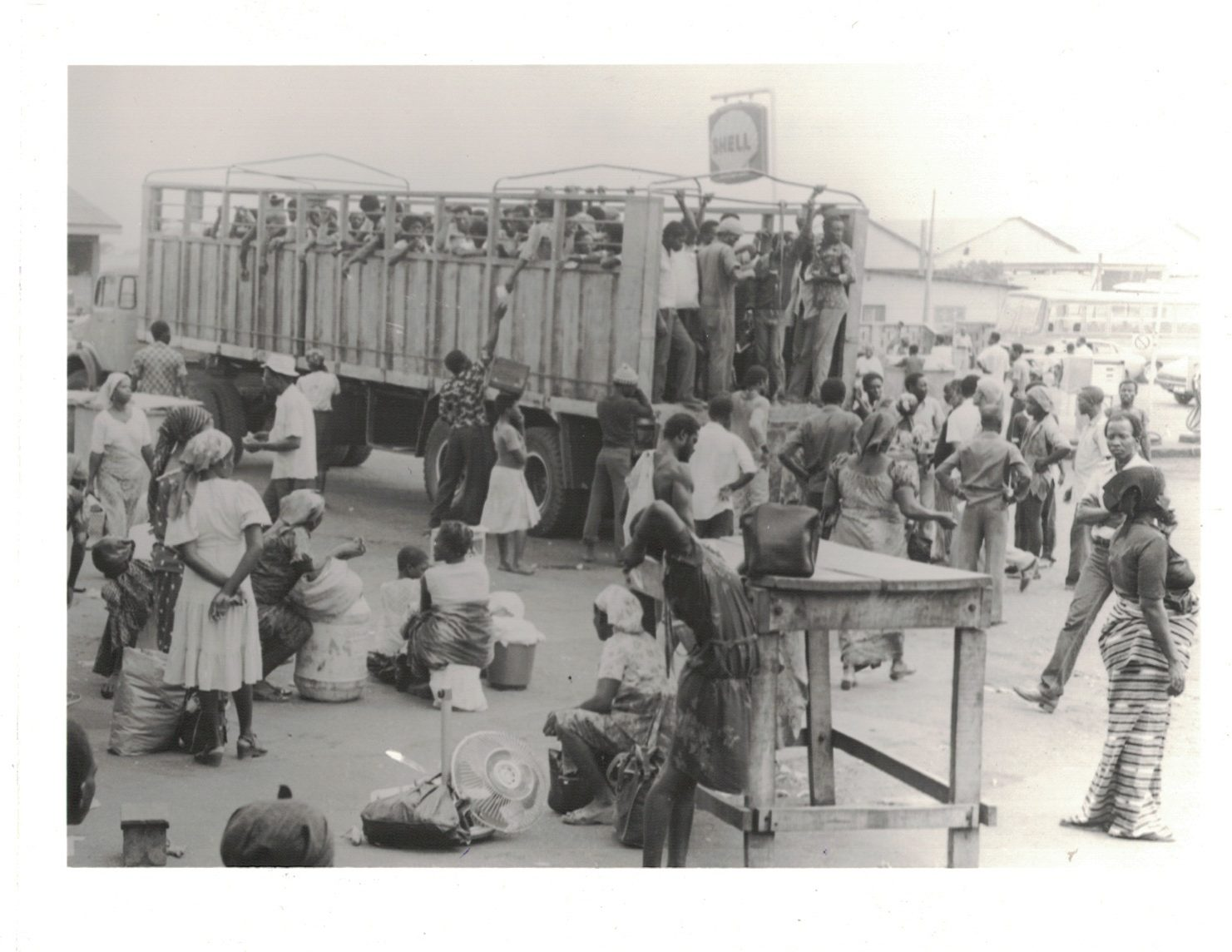 """""""Passengers boarding articulated truck at the Kaneshie/Takoradi Station,"""" Transportation Problem in Accra, 5/2/1983, Chris Briandt. Source: PS/2856/6, Photographic Section, Information Services Department, Ministry of Information, Accra, Ghana."""