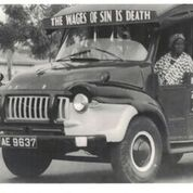 "A trader sitting in the front seat of a mammy truck with the inscription ""The Wages of Sin is Death"" -  ""Lorry Slogans,"" <em>Mate Wayo</em>, 2 March 1971. Source: PS 402/12 Photographic Section, Information Services Department, Ministry of Information, Accra, Ghana."" width=""50%"" height=""auto"">  <figcaption><small>Figure 2-a. A trader sitting in the front seat of a mammy truck with the inscription ""The Wages of Sin is Death"" – ""Lorry Slogans,"" <em>Mate Wayo</em>, 2 March 1971. Source: PS 402/12 Photographic Section, Information Services Department, Ministry of Information, Accra, Ghana. Rightsholder: Ministry of Information, Accra, Ghana.</small></figcaption></figure> <h3>Training drivers</h3> Drivers worked hard in and on their vehicles, developing wide-ranging skill and expertise. Driving was an implicitly male profession. Drivers defined the physical strength necessary to operate vehicles in poor road conditions and load goods, as well as the social and emotional control necessary to engage with passengers, as male traits even as they established formal business arrangements with female passengers or drove for female vehicle owners. Young men were trained through apprenticeships with master drivers. Families paid fees (often in some combination of alcohol, cigarettes, and cash) to the master, who promised to train the young man. Apprentices (or ""mates"") often lived in the master's household and traveled with them constantly. Daily duties included washing the vehicle, loading and unloading goods, and recruiting passengers. Throughout their daily work, mates closely observed their master's behavior to learn both the tangible, practical skills of driving and vehicular maintenance but also the more intangible social skills and cultural knowledge necessary for a successful driving career. This rigorous training often lasted 5 years or more, producing highly qualified and professional drivers who possessed not only the technical expertise necessary for driving work, but who were also integrated into a tight-knit community of drivers, defined by high levels of professionalism and, beginning in the mid-1930s, organized into unions. <figure><a href="