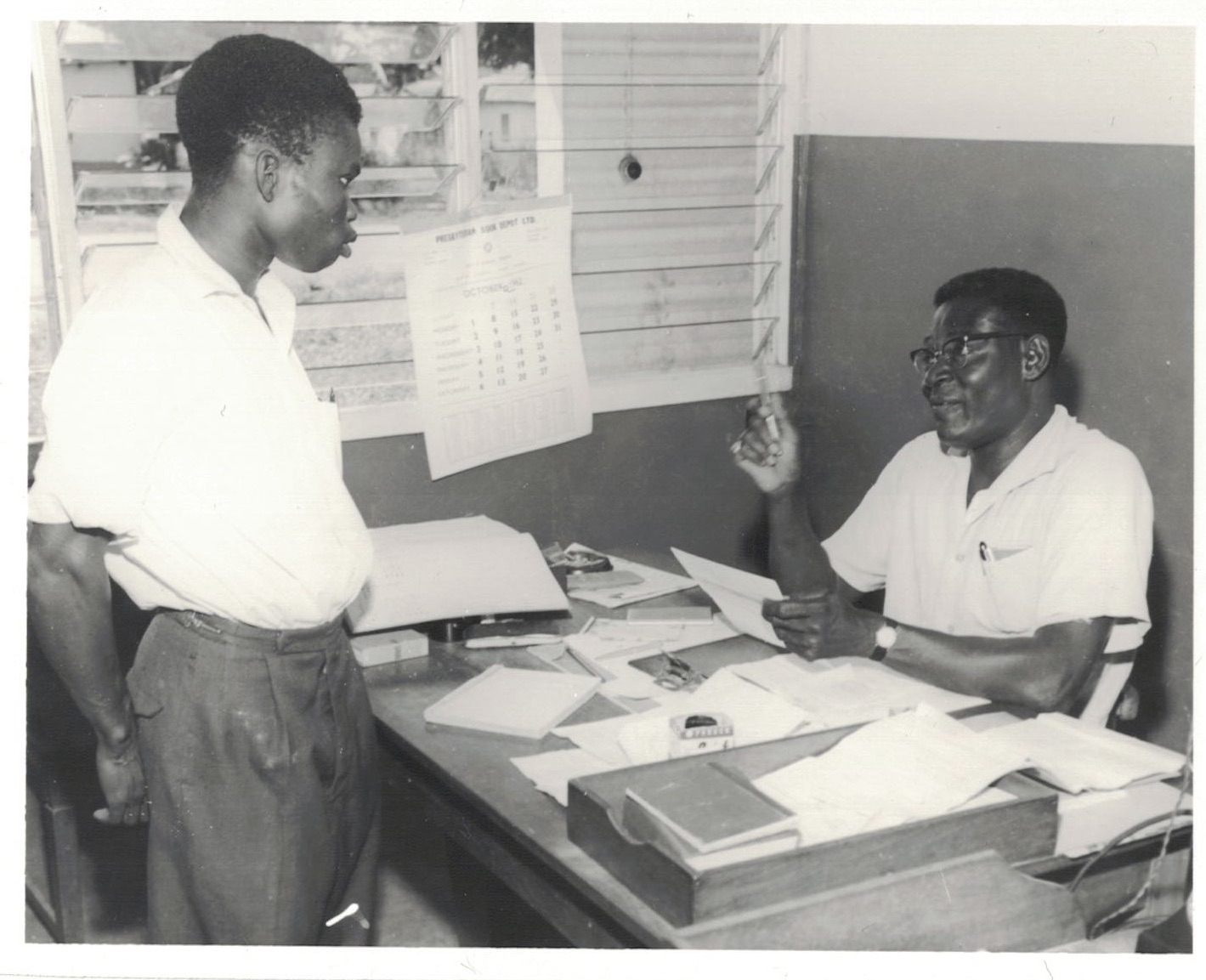"""An applicant answering questions from a Testing Officer after he has been tested on the Trunk Road."" Source: R/R/3437/7 Photographic Section, Information Services Department, Ministry of Information, Accra, Ghana."