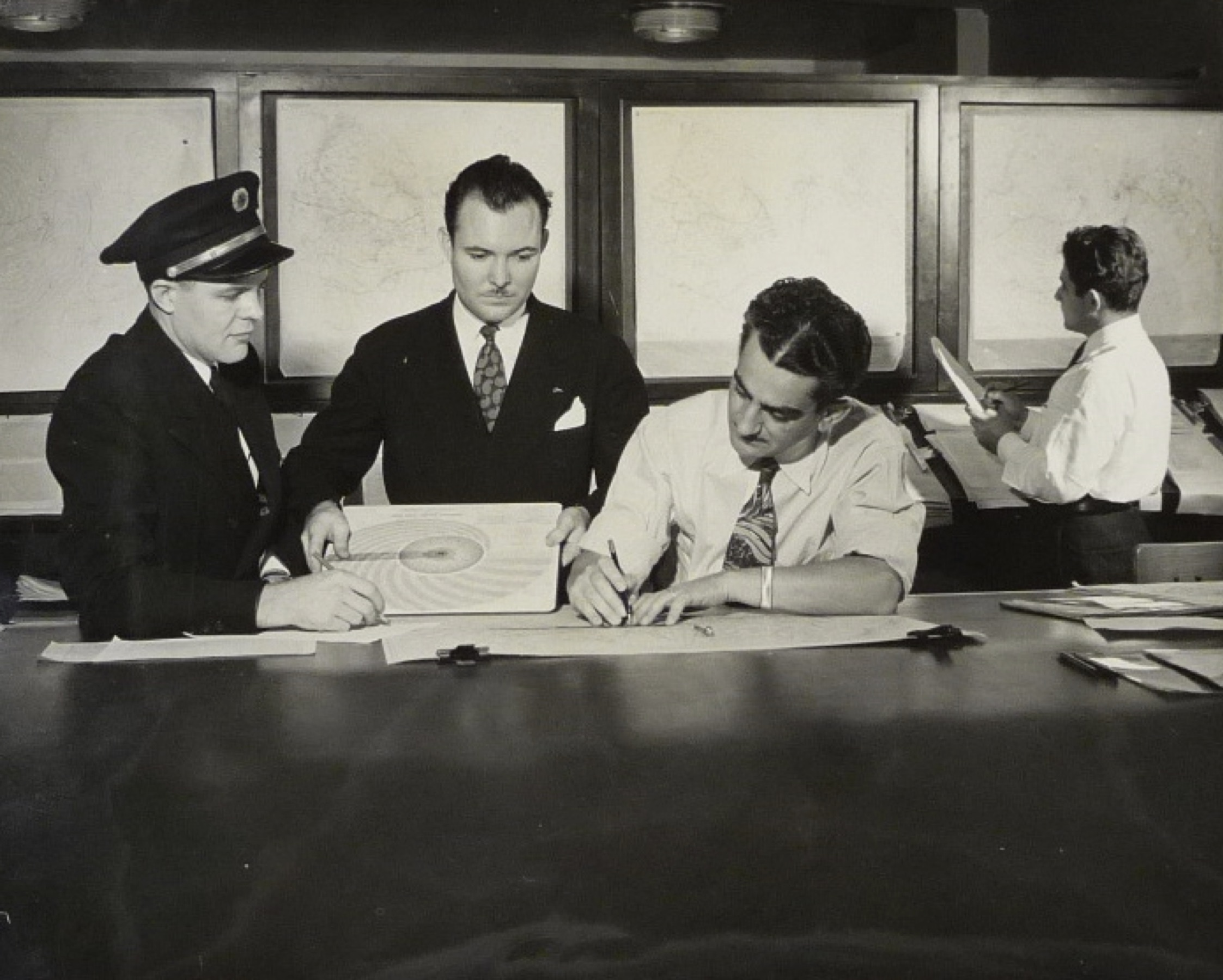 Unnamed Pan Am meteorologist (foreground right) briefs a pilot and dispatcher prior in a staged publicity photograph, c. 1939. Pan Am Airways, Inc. Records, Collection 341, Series I, Box 41 Folder 23, 'Meteorology Brochures.' Courtesy of Special Collections, University of Miami Libraries, Coral Gables, Florida.