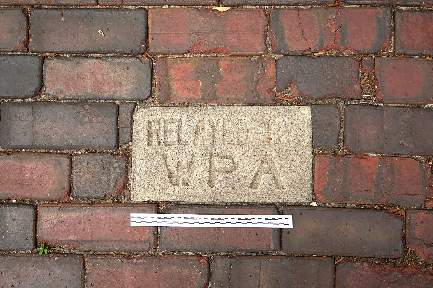 Embedded concrete plaque installed by the Works Progress Administration in the vitrified brick pavement, intersection of Woodbine Avenue and Crescent Place, Wilmette, Illinois, 2016. Photo by author.